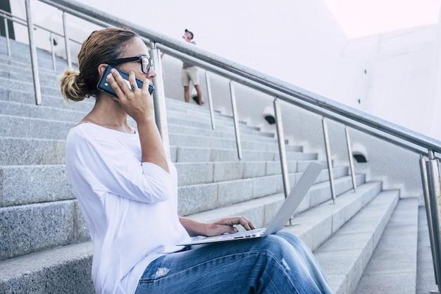 Donna caucasica adulta che lavora con tecnologia e dispositivi moderni come telefono e laptop all'aperto seduti su una scala in città urbana