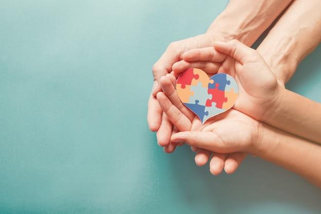 Mani per adulti e bambini che tengono a forma di cuore puzzle, consapevolezza dell'autismo, concetto di sostegno della famiglia dello spettro autistico, giornata mondiale della consapevolezza dell'autismo