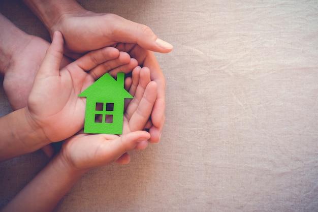 Mani dell'adulto e del bambino che tengono casa della carta verde