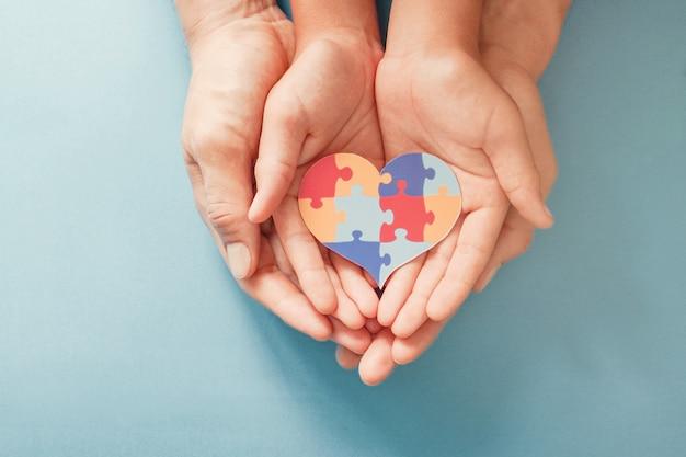 Mani del bambino e dell'adulto che tengono forma del cuore del puzzle