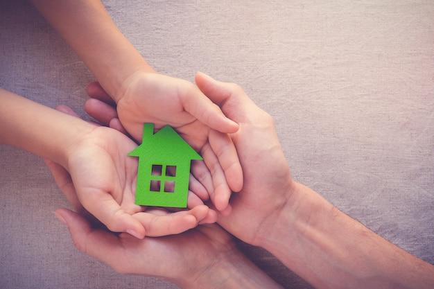Mani del bambino e dell'adulto che tengono casa di eco di carta, casa di famiglia, riparo di senzatetto e esta reale