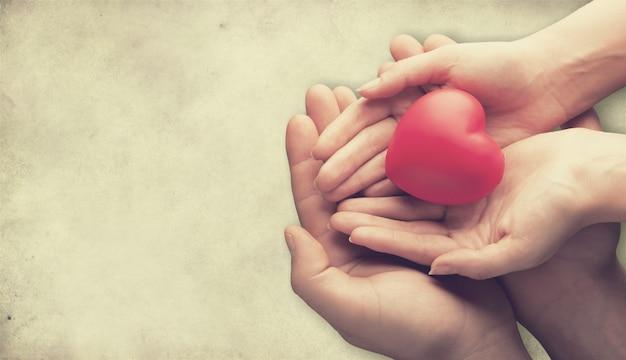Mani di adulti e bambini che tengono il cuore rosso, la salute del cuore e il concetto di donazione