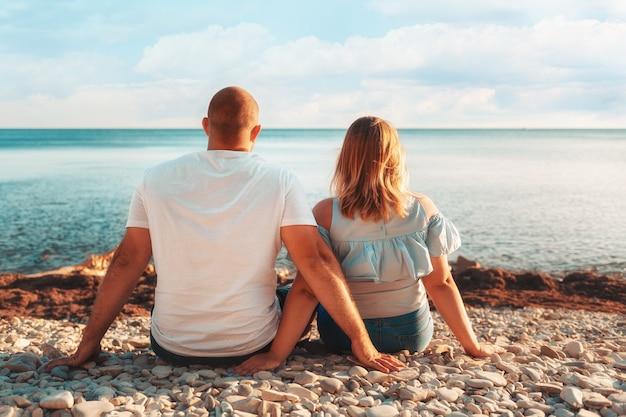 Una coppia adulta, un uomo e una donna plus size, siedono sulla spiaggia, ammirando l'oceano