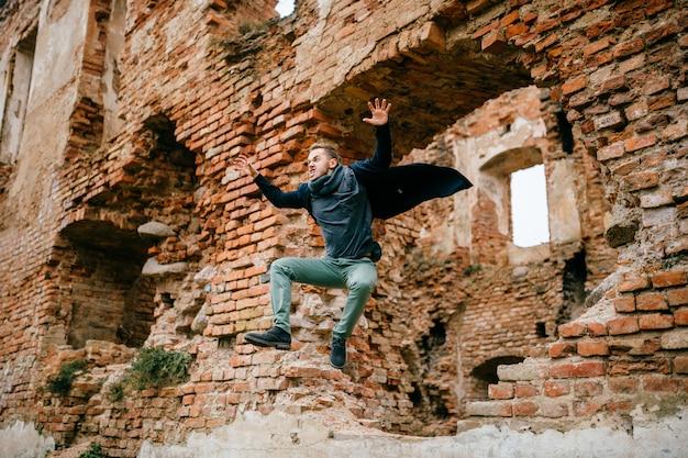Ritratto maschio emozionante insolito arrabbiato pazzo adulto. movimento di uomo d'affari in volo. giovane ragazzo con le emozioni dispari espressive comiche divertenti del fronte che saltano dal muro di mattoni.