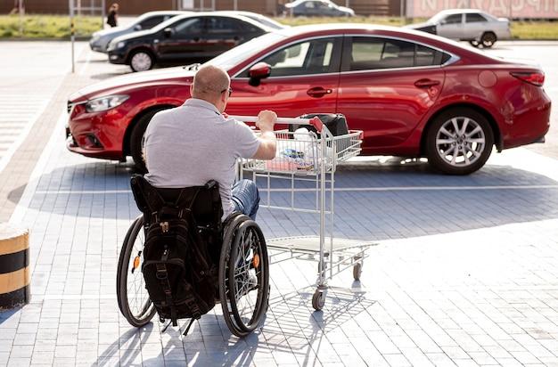 Un adulto disabile su sedia a rotelle spinge un carrello verso un'auto nel parcheggio di un supermercato
