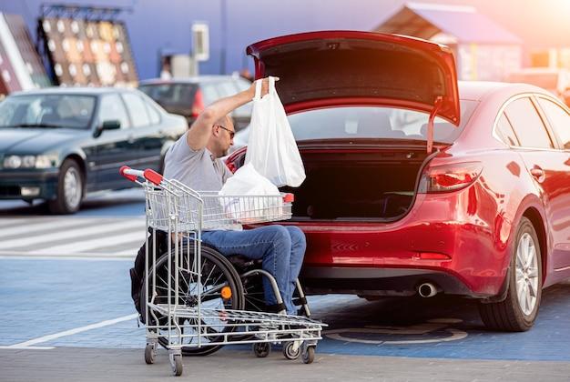Un adulto disabile su sedia a rotelle mette gli acquisti nel bagagliaio di un'auto nel parcheggio di un supermercato