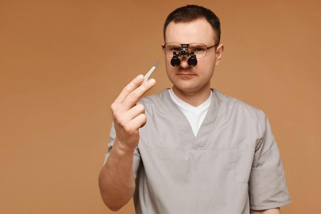 Uomo adulto medico o chirurgo in vetri di ingrandimento in posa con un bisturi