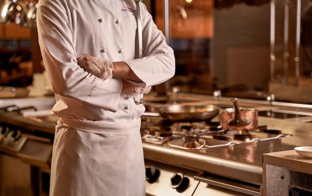 Adulto vestito in uniforme da cuoco accanto a un fornello a gas con una casseruola e una padella in piedi sui fornelli