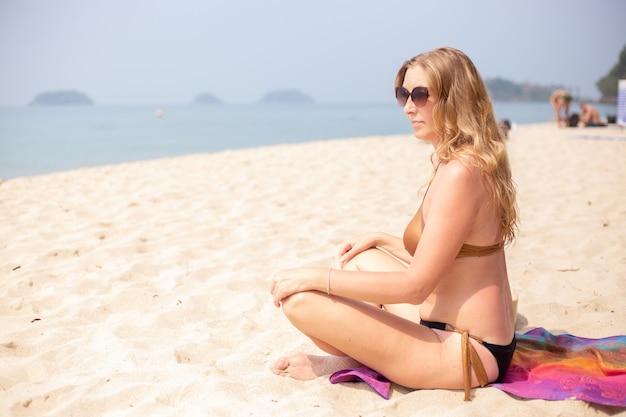 Donna europea adulta con capelli lunghi biondi si siede sulla sabbia in riva al mare nella posizione del loto