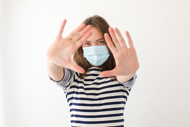 Femmina adulta in mascherina medica che guarda l'obbiettivo e gesticolando stop mentre si cerca di ottenere protezione