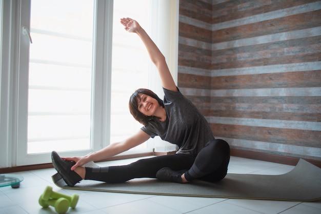 La donna esile adatta dell'adulto ha allenamento a casa. il modello femminile maturo senior si siede con le gambe larghe aperte e raggiunge una mano su. allungando tutto il suo corpo.