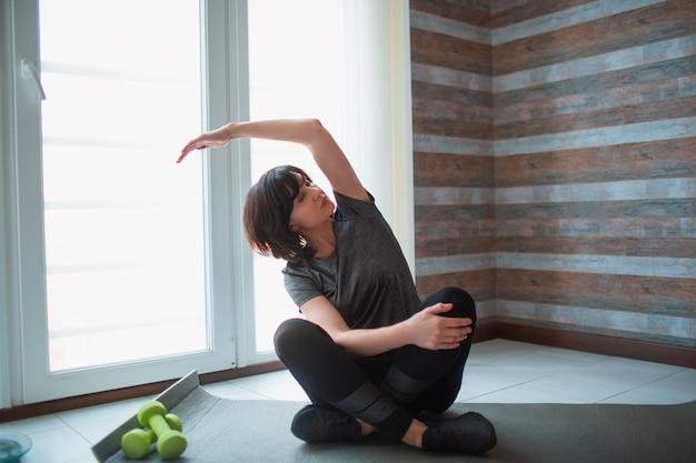 La donna esile adatta dell'adulto ha allenamento a casa. il modello senior si siede con le gambe incrociate e allunga il braccio da un lato. esercizio da solo per mettersi in forma e migliorare la salute.