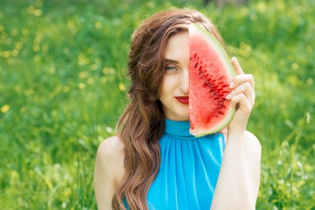 La ragazza adulta tiene il pezzo di anguria vicino alla parte del suo viso.