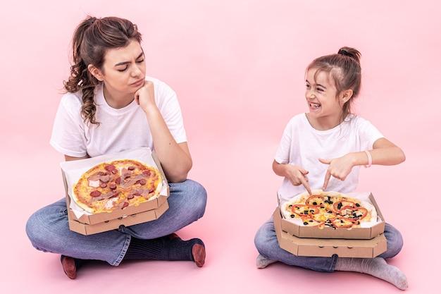 Una ragazza adulta e una bambina con diverse pizze in scatole, sfondo rosa.