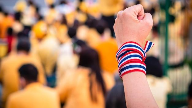Adult hand wraps thai flag sfocato sfondo thai a sostegno della monarchia thailandese.