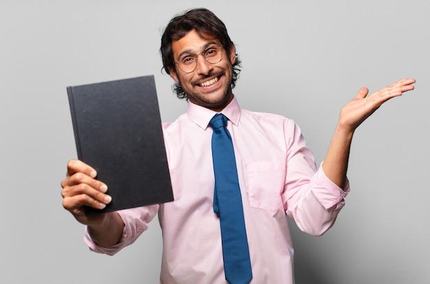 Uomo d'affari indiano bello adulto che tiene un libro