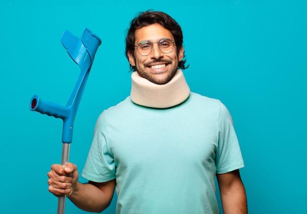 Uomo indiano bello adulto che ha subito un incidente. stampella e concetto di collare
