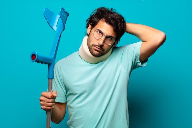 Uomo indiano bello adulto che ha subito un incidente. concetto di stampella e colletto