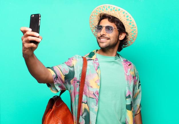 Uomo turistico indiano bello adulto che indossa fieno e una borsa di cuoio e usando il suo cellulare