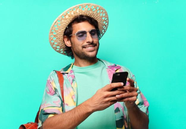 Uomo turistico indiano bello adulto che indossa fieno e una borsa di pelle e usa il suo cellulare