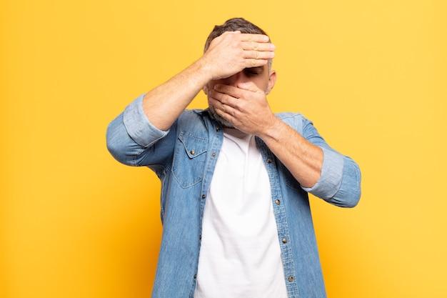 Uomo adulto bello che copre il viso con entrambe le mani dicendo no! rifiutare le immagini o vietare le foto