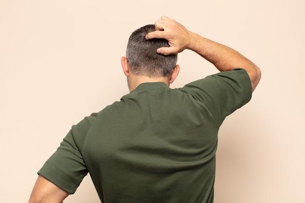 Uomo bello adulto che si sente all'oscuro e confuso, pensando a una soluzione, con la mano sull'anca e l'altra sulla testa, vista posteriore rear