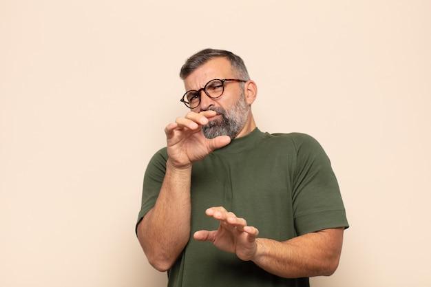 Un bell'uomo adulto che si sente disgustato e nauseato, si allontana da qualcosa di brutto, puzzolente o puzzolente, dicendo che schifo
