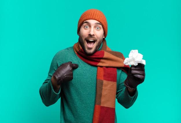 Bell'uomo adulto che si sente felice, sorpreso e orgoglioso, indicando se stesso con uno sguardo eccitato e stupito. malattia e concetto di freddo