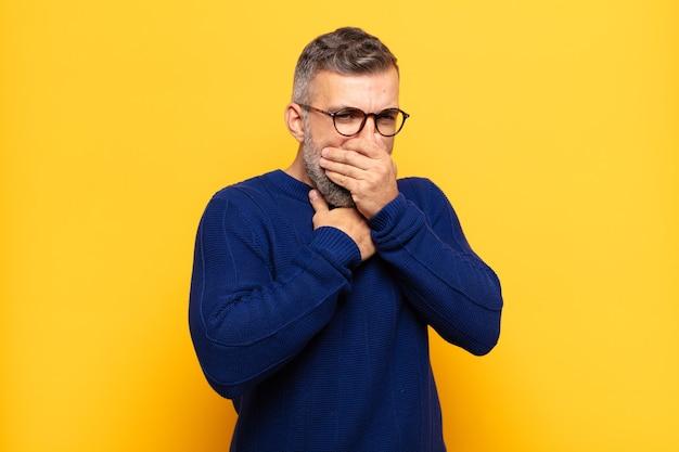 Uomo adulto bello che si sente male con mal di gola e sintomi influenzali, tosse con la bocca coperta