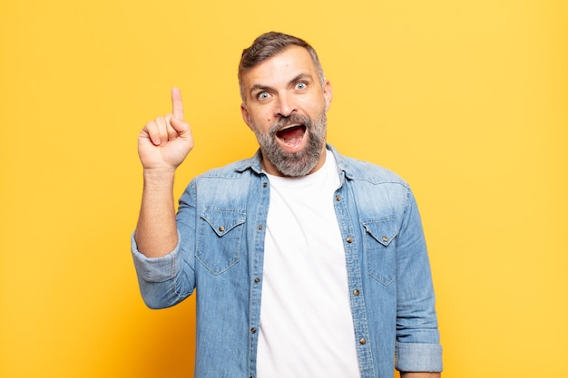 Bell'uomo adulto che si sente come un genio felice ed eccitato dopo aver realizzato un'idea, alzando allegramente il dito, eureka!