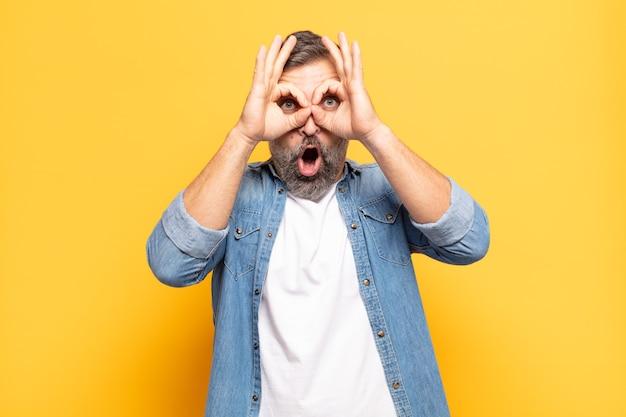 Bell'uomo adulto che si sente scioccato, stupito e sorpreso, tenendo in mano gli occhiali con uno sguardo stupito e incredulo