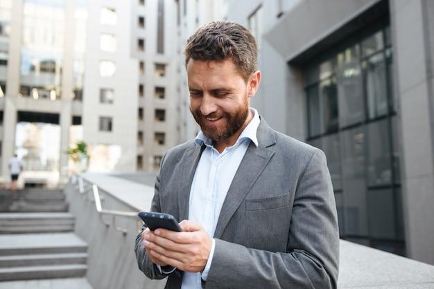 Bell'uomo adulto in abito grigio che scrive o legge un messaggio di testo nel telefono cellulare, mentre si trova di fronte al moderno edificio per uffici