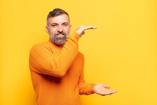 Uomo bello adulto che tiene un oggetto con entrambe le mani sullo spazio della copia laterale, mostra, offre o pubblicizza un oggetto