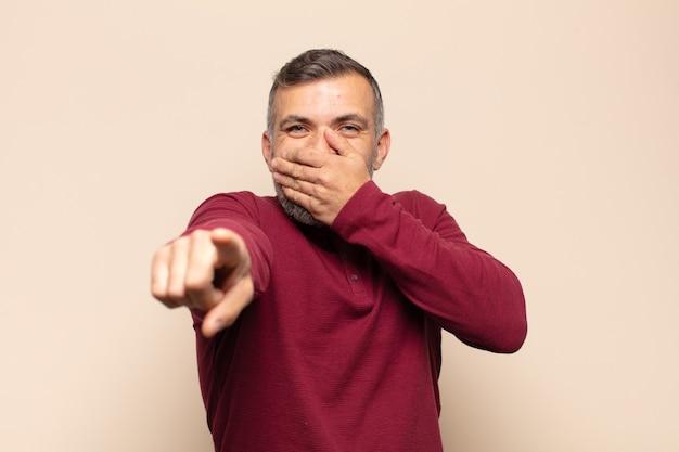 Bell'uomo adulto che ride di te, indica la telecamera e ti prende in giro o ti prende in giro