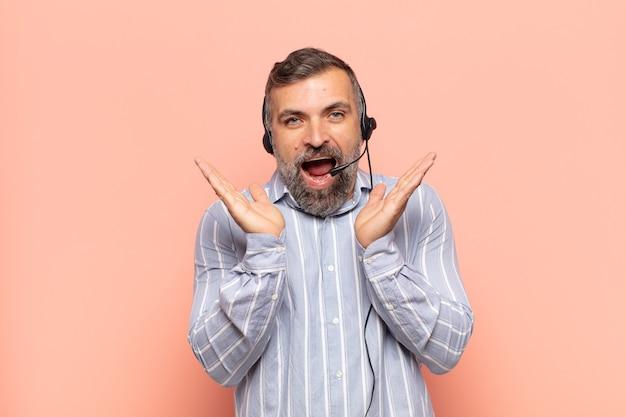 Un bell'uomo adulto che sembra felice ed eccitato, scioccato da una sorpresa inaspettata con entrambe le mani aperte accanto al viso