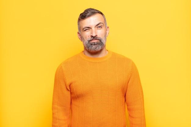 Bell'uomo adulto che sembra felice e amichevole, sorridente e ammiccante con un atteggiamento positivo Foto Premium