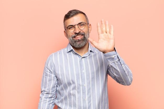 Bell'uomo adulto che sorride allegramente e allegramente, agitando la mano, dandoti il benvenuto e salutandoti o salutandoti