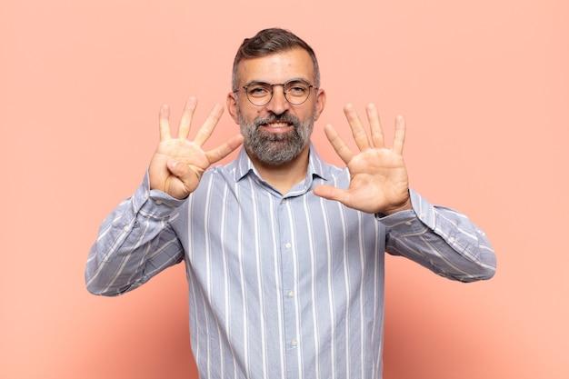 Uomo adulto bello sorridente e guardando amichevole, mostrando il numero nove o nono con la mano in avanti, conto alla rovescia