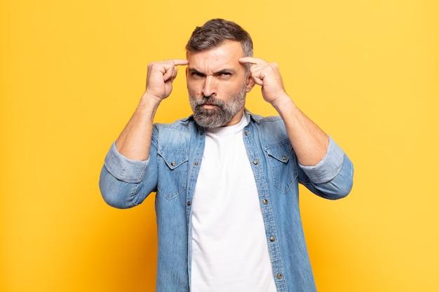 Bell'uomo adulto con uno sguardo serio e concentrato, che fa brainstorming e pensa a un problema impegnativo