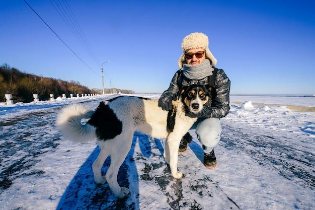 Uomo felice adulto che posa con il cane amichevole nel campo di neve