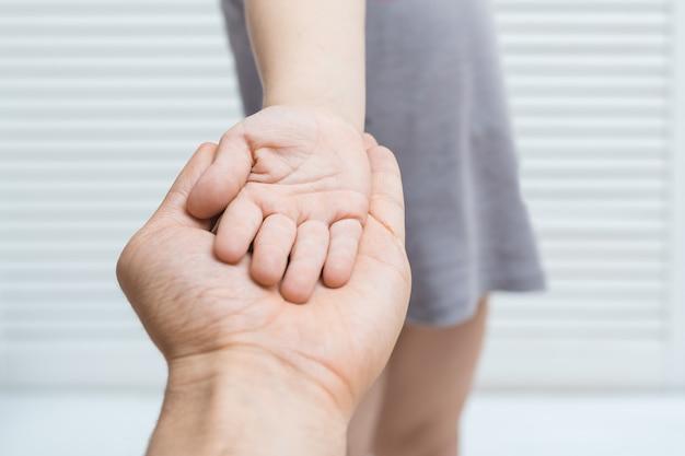 Adulto che tiene la mano del bambino. il palmo del bambino e quello dell'adulto insieme.