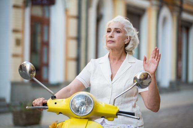 Signora adulta su uno scooter.