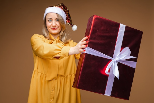 Signora adulta in un vestito giallo e un cappello della santa con le scintille che pongono un regalo di natale, avvolto in un grande pacchetto. anno nuovo concetto