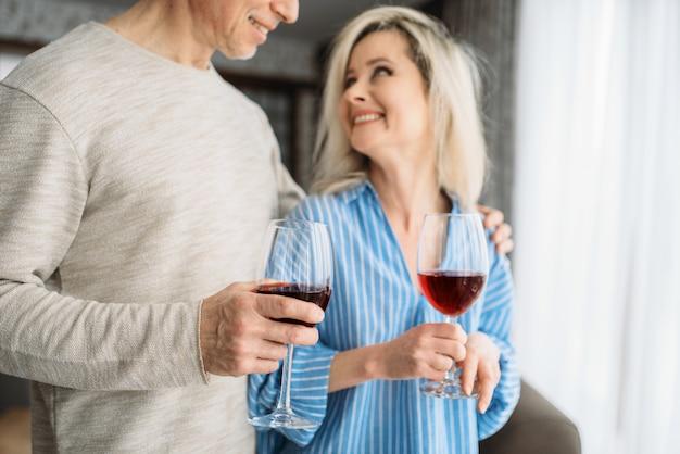 La coppia adulta di amore beve vino rosso a casa. marito e moglie maturi hanno una cena romantica, famiglia felice