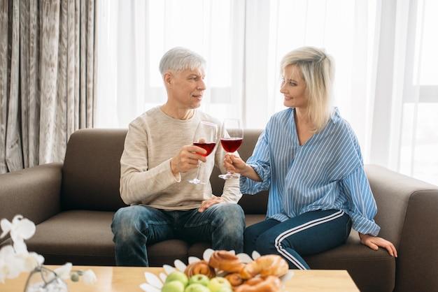 Coppia adulta amore seduto sul divano e beve vino rosso a casa. marito e moglie maturi hanno una cena romantica, famiglia felice