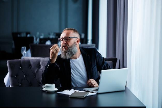 Un uomo d'affari adulto sta lavorando a un nuovo progetto e sta guardando i grafici di crescita delle azioni. si siede al tavolo vicino alla grande finestra. guarda lo schermo del laptop e beve caffè.