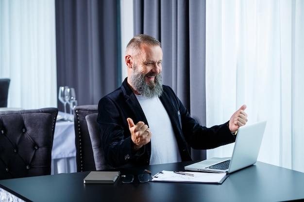 Un uomo d'affari adulto sta lavorando a un nuovo progetto e sta guardando i grafici di crescita delle azioni. si siede al tavolo vicino alla grande finestra. guarda lo schermo del laptop e sorride