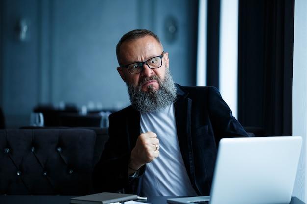 Un uomo d'affari adulto sta lavorando a un nuovo progetto e sta guardando i grafici di crescita delle azioni. si siede al tavolo vicino alla grande finestra. guarda lo schermo del laptop