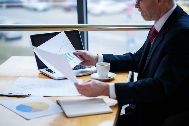 Uomo d'affari maschio adulto che lavora su un nuovo progetto e guarda i grafici di crescita delle scorte. si siede a una grande finestra al tavolo. guarda lo schermo del laptop e beve caffè.