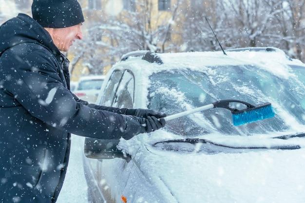 Maschio adulto pulire il parabrezza dell'auto dalla neve nella bufera di neve b